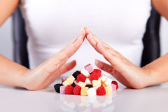Hands over a pyramid of candies Stock Images