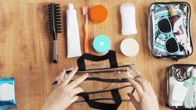 Hands packing cosmetic bag with stuff for travel stock video
