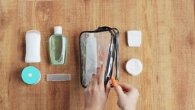 Hands packing cosmetic bag for travel stock video footage