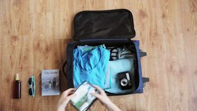 Hands packing travel bag with personal stuff. Tourism, people, luggage and clothing concept - hands packing travel bag with personal stuff stock video footage