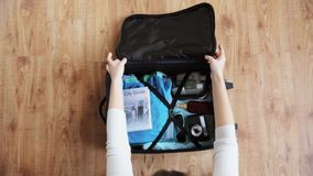 Hands packing travel bag with personal stuff stock video footage