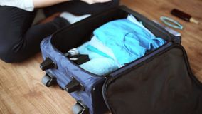 Hands packing travel bag with personal stuff. Tourism, people, luggage and clothing concept - hands packing travel bag with personal stuff stock footage