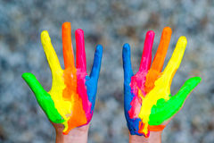 Hands painted in colorful paints ready for hand prints. Very shallow depth of field - only hands are sharp stock image