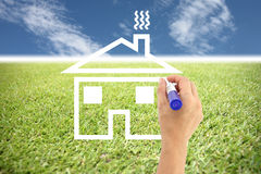 Hands are painted house on grass and blue sky. Stock Photo