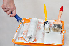 Hands painter dunks roller brush in tray of white paint. House painting supplies, painter tools in an orange tray with white paint, roller brush and stock images