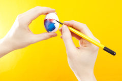 Painting Easter Eggs. Hands Painting Easter Eggs with a Paintbrush on Yellow Background Royalty Free Stock Photos