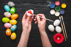 Hands painting eggs for Easter holiday on wooden table Royalty Free Stock Images