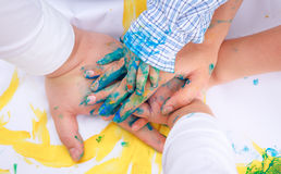 Hands in paints on paper Royalty Free Stock Photos