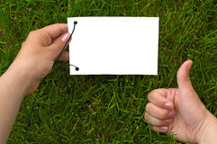 Hands and paper on grass Royalty Free Stock Image