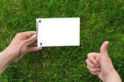 Hands and paper over grass. Hands with thumb up and white paper over grass Royalty Free Stock Photo