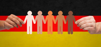 Hands with paper people pictogram over german flag. Community, unity, population, race and humanity concept - multiracial couple hands holding chain of paper Royalty Free Stock Photos