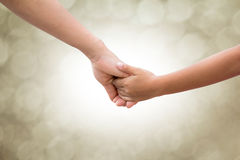 In the hands of parents and children on a background blur bokeh. Mother arrested for baby care style sepia tone. Stock Photography
