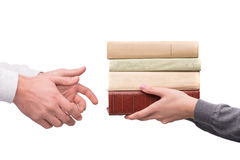 Hands passing heap of books Stock Photo