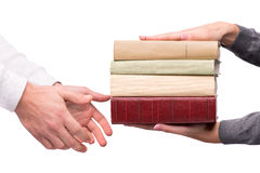Hands passing heap of books Stock Photos