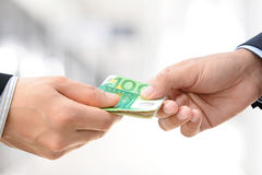 Hands passing money - Euro (EUR) bills Stock Photo