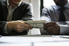 Hands passing money under table corruption bribery Stock Image