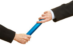 Hands passing relay baton. Two hands passing a blue relay baton stock photo