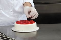 Hands pastry chef prepares a cake, cover with icing and decorate with strawberries, works on a stainless steel kitchen stock photography