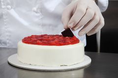 Hands pastry chef prepares a cake, cover with icing and decorate with strawberries, works on a stainless steel kitchen royalty free stock photography