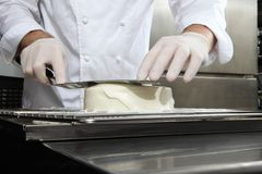 Hands pastry chef prepares a cake, cover pouring white icing, working on a stainless steel kitchen work top stock photo