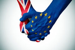 Hands patterned with the British and the European flag. Two persons holding hands patterned with the flag of the United Kingdom and the flag of the European Stock Images