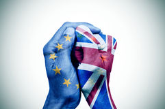 Hands patterned with the European and the British flag put toget. Hand patterned with the flag of the European Community envelops another hand patterned with the Royalty Free Stock Photography