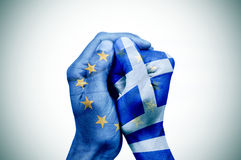Hands patterned with the European and the Greek flag put togethe. Hand patterned with the flag of the European Community envelops another hand patterned with the Royalty Free Stock Photography