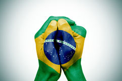 Hands patterned with the flag of Brazil. Closeup of the hands of a young man put together patterned with the flag of Brazil against a white background, with a Stock Image
