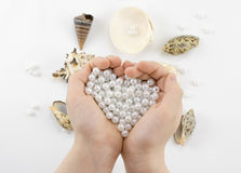 Hands with pearl beads and seashells Stock Photos