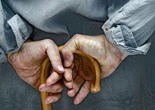 Hands of peasant. Farmer hands, leaning on a cane placed on his back Stock Photography