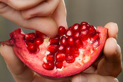 Hands peeling pomegranate, closeup Royalty Free Stock Images