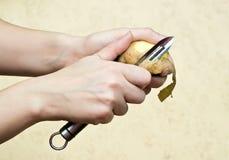 Hands peeling potato. With peeler Stock Images