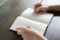 Hands with pencil and book Royalty Free Stock Image