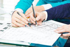 Hands with pencil solving sudoku Stock Photo