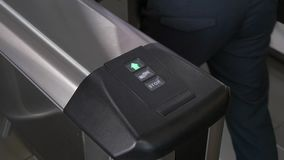 Hands of people apply electronic pass to turnstile wicket checkpoint in office. Modern equipment of access system in business center closeup. Macro video stock footage