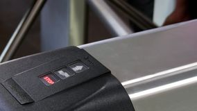 Hands of people apply electronic pass to turnstile wicket checkpoint in office. Modern equipment of access system in business center closeup. Macro video stock video footage