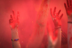 Hands of people in a crowd. Being raised within cloud of colour dust royalty free stock photos