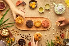 Teats for mid autumn festival. Hands of people eating tasty round moon cakes at mid autumn festival stock images