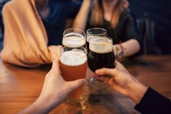 Hands of people holding beer and cheering in brewery pub. people. Toasting with delicious beer  in bar. friends drinking and enjoying a beer. leisure and Royalty Free Stock Photos