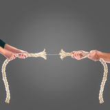 Hands of people pulling the rope on black background. Competition concept Stock Photos