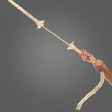 Hands of people pulling the rope on black background. Competition concept Stock Photo