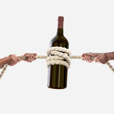 Hands of people pulling the rope bottle of wine on white background. Competition concept. Hands of people pulling the rope on white background royalty free stock photo