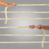 Hands of people pulling the rope on a gray background.  Competition concept. Hands of people pulling the rope. Cooperation concept Stock Photography