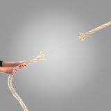 Hands of people pulling the rope on a gray background.  Competition concept Royalty Free Stock Photography