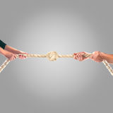 Hands of people pulling the rope on a gray background. Cooperation concept Stock Photo