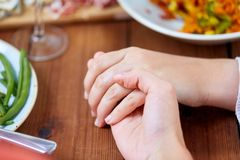 Hands of people at table praying before meal. People, relationships and eating concept - hands of people sitting at table with food and praying before meal Stock Image
