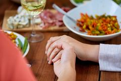 Hands of people at table praying before meal. People, relationships and eating concept - hands of people sitting at table with food and praying before meal Stock Photos