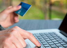 Hands of person entering credit Card Data on Laptop. Computer Internet shopping or booking Cup of Coffee on wooden background Stock Photo