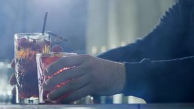 Hands of person exhibit beautiful freshly prepared drinks with berries on foreground. In light haze stock footage