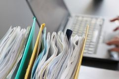 Hands of person typing on laptop computer with binders filled with papers  in foreground. Selective focus royalty free stock image